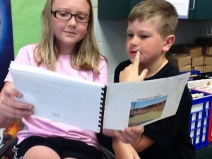 Two children reading by sharing a book.